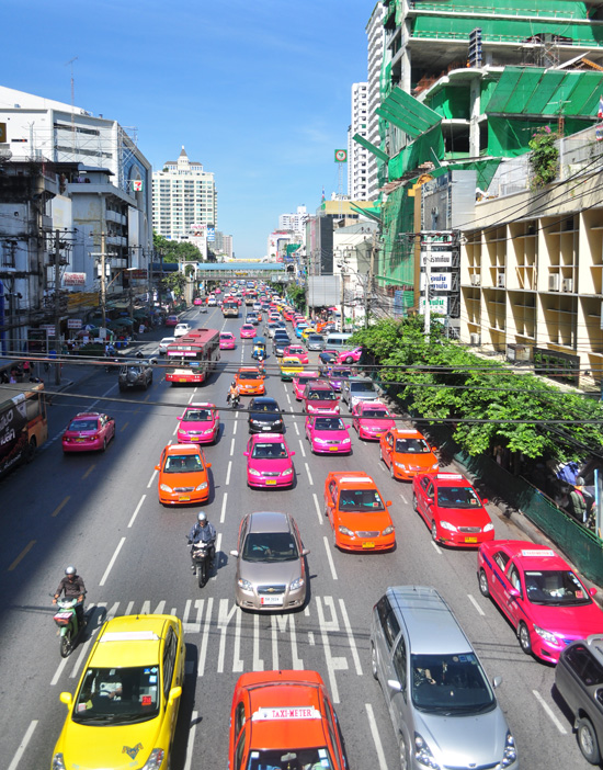 Colourful taxis driving down Petchburi Road Bangkok